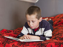 Young boy reding a book Stock Image