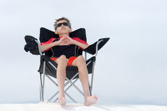 Young boy relaxing. In beach chair on sand dune Stock Photo