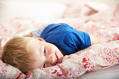 Young Boy Relaxing On Bed Stock Images
