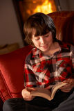 Young Boy Relaxing With Book By Cosy Log Fire. Sitting on sofa on winter vacation Royalty Free Stock Image