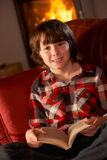 Young Boy Relaxing With Book By Cosy Log Fire. Smiling At Camera Stock Photos