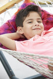 Young Boy Relaxing In Garden Hammock Together Stock Photo