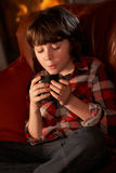 Young Boy Relaxing With Hot Drink By Cosy Log Fire. Sitting on sofa during winter vacation Stock Photography