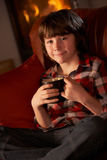 Young Boy Relaxing With Hot Drink By Cosy Log Fire Royalty Free Stock Photography