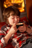 Young Boy Relaxing With Hot Drink By Cosy Log Fire Royalty Free Stock Images
