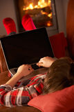 Young Boy Relaxing With Laptop By Cosy Log Fire Stock Photo