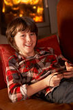 Young Boy Relaxing With MP3 Player. By Cosy Log Fire smiling at camera Royalty Free Stock Images