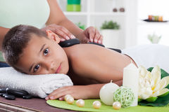 Young boy  relaxing in spa. stone massage. Royalty Free Stock Image