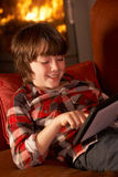 Young Boy Relaxing With Tablet Computer Stock Image