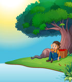 A young boy relaxing under the tree Royalty Free Stock Photography