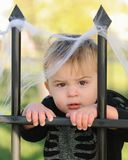 Young boy resting against fence Stock Photo
