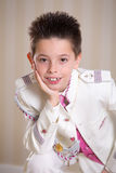 Young boy resting his head on his hand in his First Holy Communi Royalty Free Stock Images