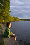 Young boy resting at lake side. Boy looking out towards sunset Royalty Free Stock Images