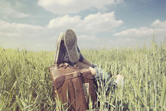 Young boy resting in a meadow with his feet above his suitcase Stock Photo