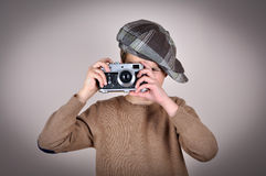 Young boy with retro camera. Cute young boy wearing a brown sweater and tartan newsboy cap taking a picture with retro camera.  on gray background and added Stock Photo