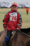 Young boy rides during Naadam. KARKORIN, MONGOLIA, July 8, 2013 : Young boy rides during Naadam. Naadam is a traditional festival where Mongolian wrestling Royalty Free Stock Image