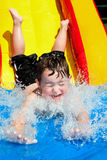 Young boy rides water slide Royalty Free Stock Image