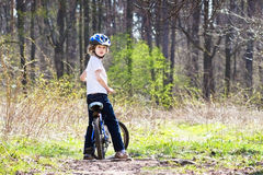 Young boy riding a bike in the forest Stock Photos