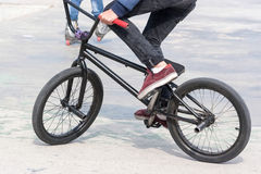 Young boy riding his BMX bike near ramps Royalty Free Stock Photos