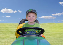 Young Boy on a Riding Mower. A young boy sitting on a riding mower outside in the field Stock Photos
