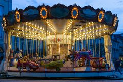 Young boy riding old carousel at night with bright lights stock images