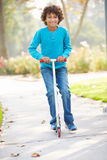 Young Boy Riding Scooter In Park Stock Photos