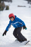 Young boy riding snowboard Stock Image