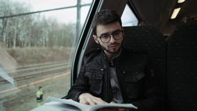 Young boy riding train and reading book. Boy with glasses. 4K. Young boy riding metro train and reading book stock footage