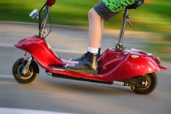 Young boy riding a vintage electric scooter Stock Photo
