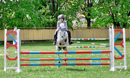 Young boy riding white horse. Young children jockey riding beautiful racial white aristocratic England horse in parkour competition Stock Photo