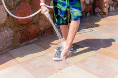 Young boy rinsing beach sand off his legs. And shoes with a hose pipe at a seaside resort on his summer vacation Royalty Free Stock Photos