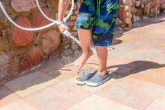 Young boy rinsing beach sand off his legs Royalty Free Stock Photography