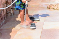Young boy rinsing off his feet and shoes. To get rid of the salt and sand after spending the day at the beach at a seaside resort on summer vacation Stock Photography