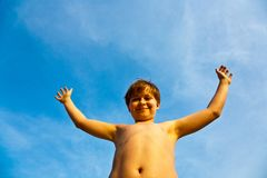 Young boy rises his arms at the beach Royalty Free Stock Image