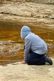 A young boy at a rivers edge watching water flowing.  Stock Photo