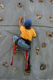 Young boy rock climbing. On man-made rock wall Stock Photography