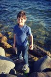 Young Boy On Rocks by Lake Royalty Free Stock Photos