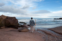 Young boy on a rocky beach stares out to sea Stock Photography