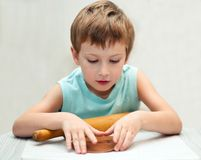 Young boy rolling gingerbread dough. And making christmas cookies Stock Photo