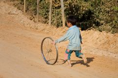 Boy playing with wheel, Laos royalty free stock images
