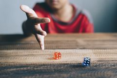 Young boy rolling / throwing a dice. Lifestyle concept. gambling concept. board games Royalty Free Stock Images