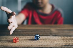 Young boy rolling / throwing a dice. Lifestyle concept. gambling concept. board games Stock Images