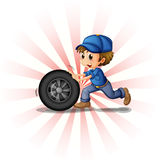 A young boy rolling a tire Stock Photos