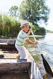 Young man rowing a boat. Young boy rowing oar standing in boat on the river Royalty Free Stock Photos