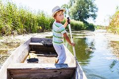 Young man rowing a boat. Young boy rowing oar standing in boat on the river Royalty Free Stock Image
