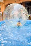 Young boy in rubber ball floating on water Royalty Free Stock Images