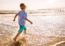 Young boy run on the shore Stock Images