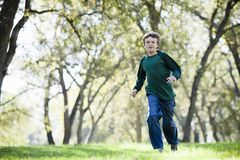 Young Boy Running. In The Grass in a Park Royalty Free Stock Image
