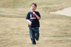 Young Boy Running. A young boy running outdoors on grass Royalty Free Stock Image
