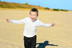 Young boy running. Happy boy running on the empty beach Stock Image